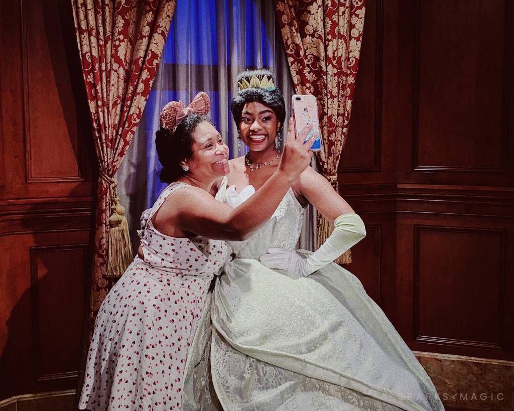 Black woman taking a selfie with Disney character Princess Tiana at Walt Disney World experiencing Part of the Disney Magic