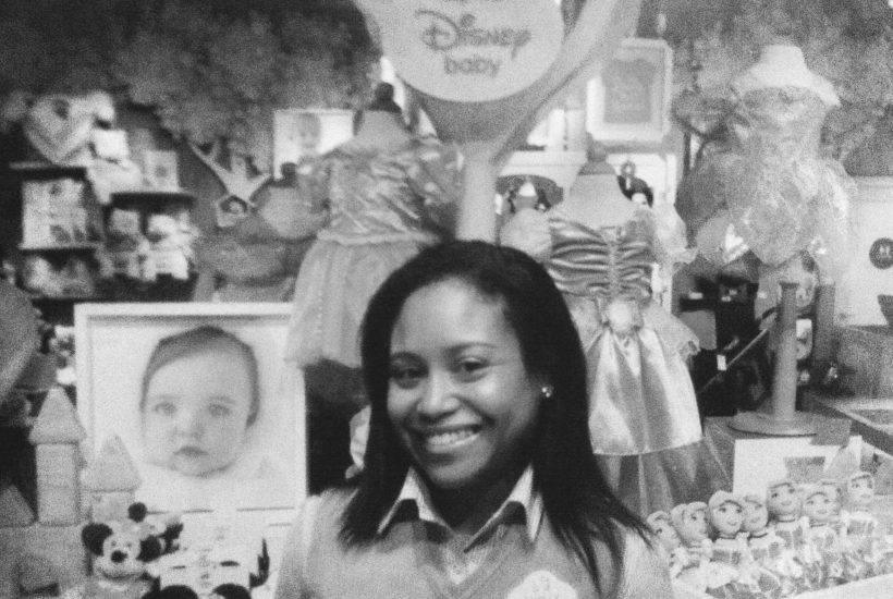 Biracial female Disney cast member smiling at work in the Disney Baby Store