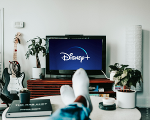 Viewer's feet resting on a coffee table with the tv showing Disney+ streaming service.
