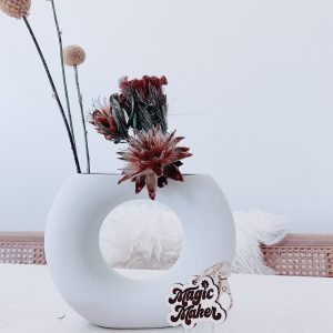 """Diamond geo shaped essential oil roller bottle keychain with wood charm engraved with the words """"Magic Maker"""" next to a vase of dried flowers."""