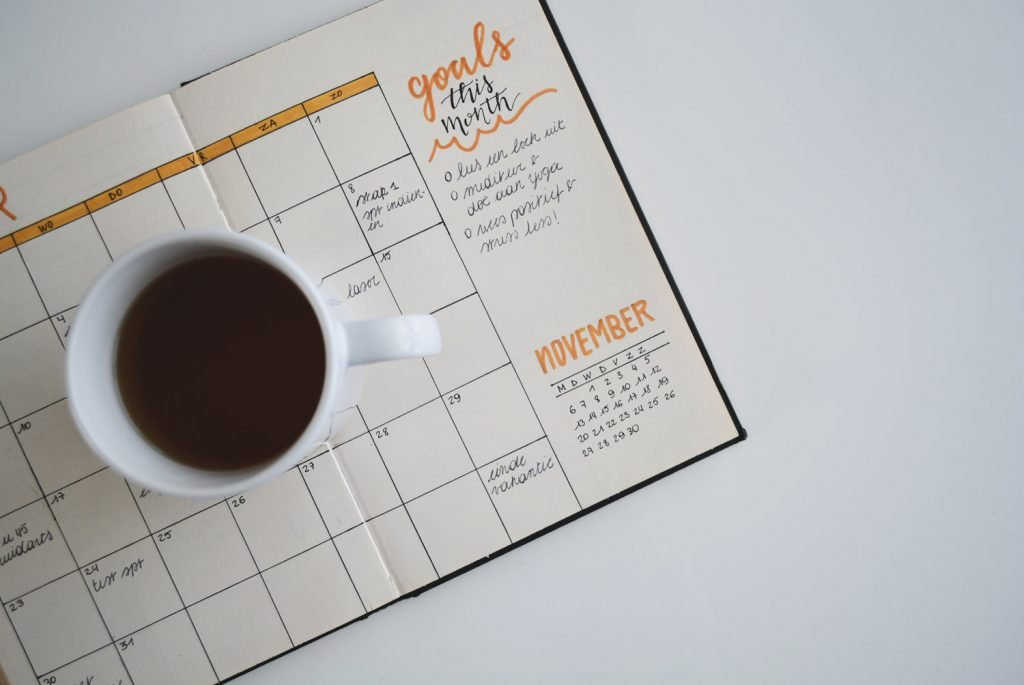 White background with planner opened to a calendar and a coffee mug sits on top of the open planner.